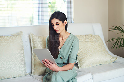 Buy stock photo Shot of an attractive young woman using her tablet while relaxing at home