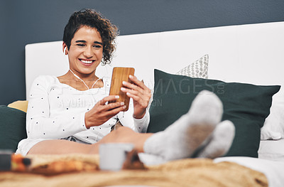 Buy stock photo Full length shot of an attractive young woman sitting on her bed and using her cellphone while at home