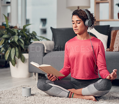 Buy stock photo Full length shot of an attractive young woman sitting and listening to music while reading in her living room