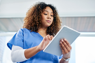 Buy stock photo Shot of an attractive young female nurse using a digital tablet while working at a hospital