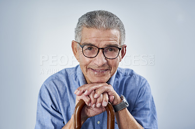 Buy stock photo Portrait of a cheerful senior man smiling and leaning on his walking stick against a grey background