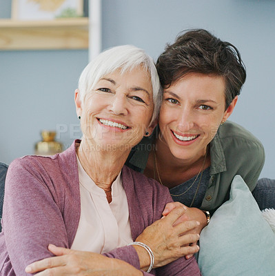 Buy stock photo Cropped portrait of an attractive young woman hugging her happy senior mother while at home