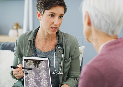 Buy stock photo Cropped shot of an attractive young woman showing a senior patient her medical results on a tablet while sitting down