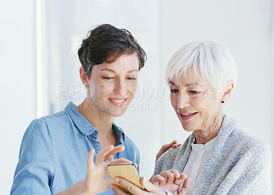 Buy stock photo Cropped shot of a senior woman holding a cellphone while talking with her attractive young daughter while at home