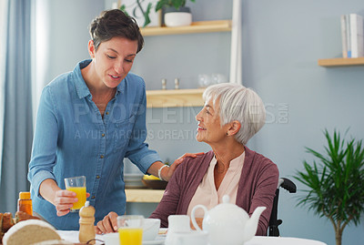 Buy stock photo Cropped shot of a happy senior woman sitting and having breakfast with her attractive young daughter while at home