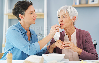 Buy stock photo Cropped shot of an attractive young woman wiping her senior mother's mouth while they have breakfast together at home