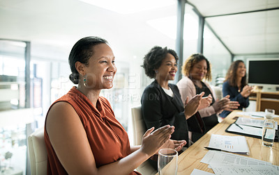 Buy stock photo Shot of a group of businesswomen clapping during a meeting in a modern office
