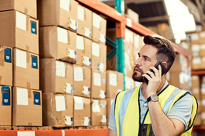 Buy stock photo Shot of a young man talking on a cellphone while working in a warehouse