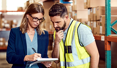 Buy stock photo Shot of a young man and woman going through notes on a clipboard in a warehouse