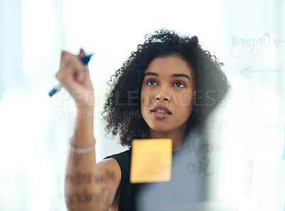 Buy stock photo Cropped shot of an attractive young businesswoman writing notes on a glass wall in a modern office