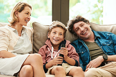 Buy stock photo Shot of an adorable young boy watching tv with his parents on the sofa at home