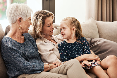 Buy stock photo Shot of a happy senior woman relaxing on the sofa with her daughter and granddaughter at home