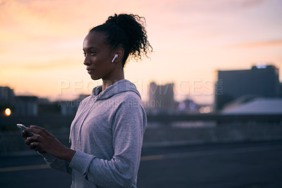 Buy stock photo Cropped shot of an attractive young woman wearing earphones and using her cellphone before going for a morning run