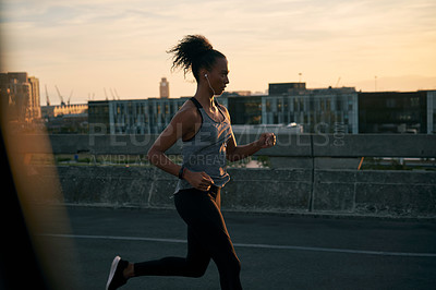 Buy stock photo Cropped shot of an attractive young woman wearing earphones and running while outdoors in the city during sunrise