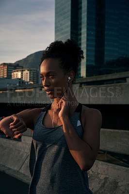 Buy stock photo Cropped shot of an attractive young woman wearing earphones and checking her pulse after running in the morning