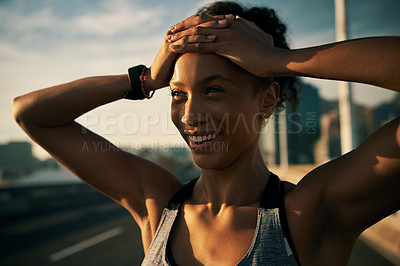 Buy stock photo Cropped shot of an attractive young woman standing outside with her arms over her head after her morning run
