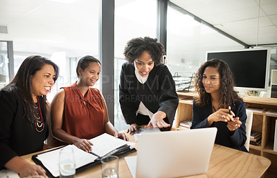 Buy stock photo Shot of a group of young businesswomen using a laptop together during a boardroom meeting