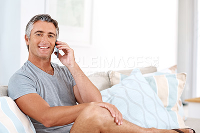 Buy stock photo Cropped portrait of a handsome mature man sitting on his living room sofa alone and talking on his cellphone