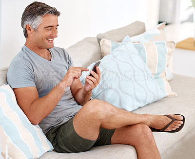 Buy stock photo Cropped shot of a handsome mature man sitting on his living room sofa and using his cellphone during the day