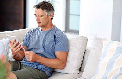 Buy stock photo Cropped shot of a handsome mature man sitting on his living room sofa and using a tablet during the day