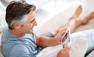 Buy stock photo Cropped shot of a handsome mature man using a tablet while sitting on his living room sofa