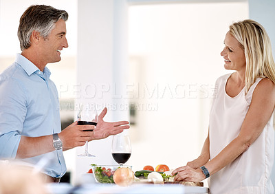 Buy stock photo Cropped shot of a mature couple enjoying wine and talking while making dinner together