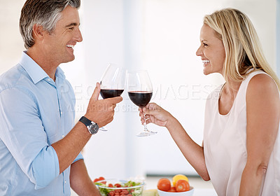 Buy stock photo Cropped shot of an affectionate mature couple toasting with red wine while making dinner