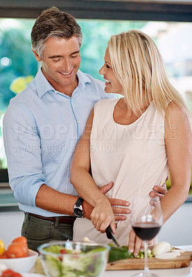 Buy stock photo Cropped shot of an affectionate mature couple cooking dinner together in the kitchen