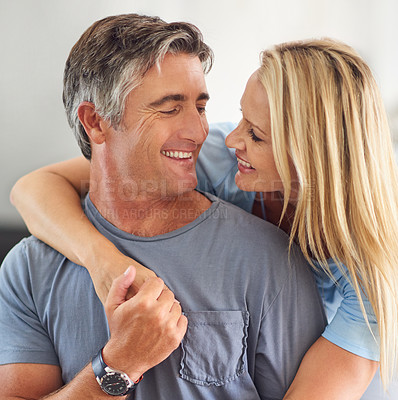 Buy stock photo Cropped shot of a happy mature couple hugging each other while in the living room during the day