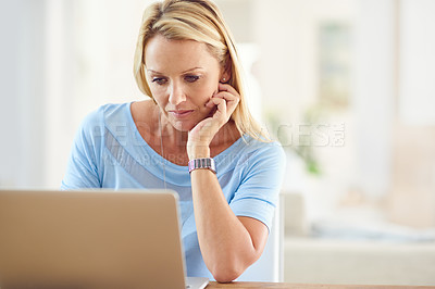Buy stock photo Cropped shot of an attractive mature woman sitting and using a laptop while in her living room during the day