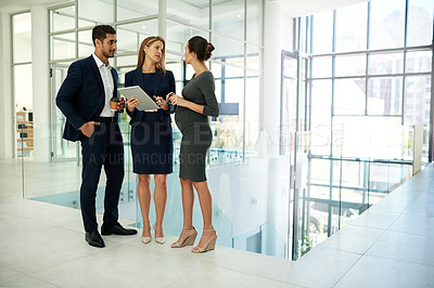 Buy stock photo Full length shot of a group of young businesspeople standing together in a modern office and using a tablet