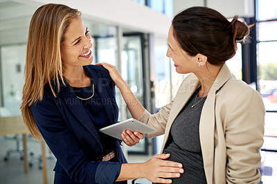 Buy stock photo Cropped shot of an attractive young businesswoman rubbing her attractive young coworker's pregnant stomach while standing in a modern office