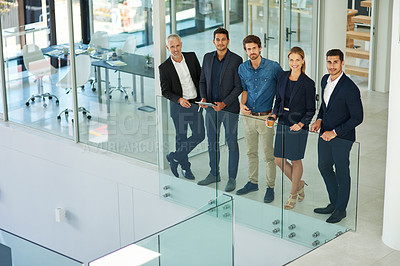 Buy stock photo Full length shot of a diverse group of businesspeople standing together in a modern office during the day