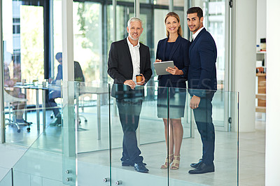 Buy stock photo Full length portrait of a group of young businesspeople standing together in a modern office and using a tablet