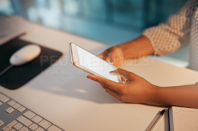 Buy stock photo Shot of an unrecognizable businesswoman using a cellphone while working late in her office