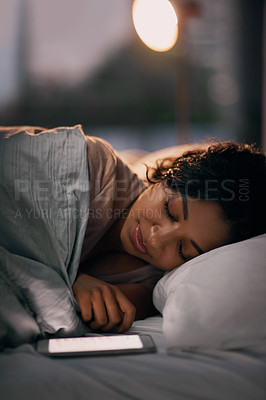 Buy stock photo Shot of a beautiful young woman sleeping next to her cellphone in her bed at home during the night