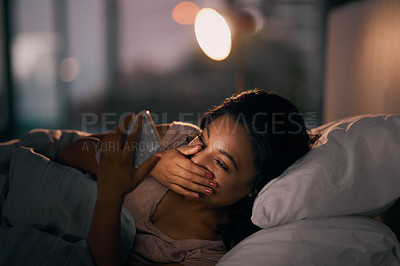 Buy stock photo Shot of a beautiful young woman using her cellphone in her bed at home during the night