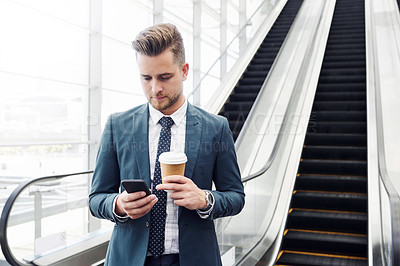 Buy stock photo Cropped shot of a handsome young businessman using a smartphone while standing alone in the workplace