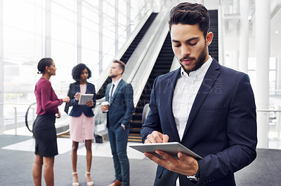Buy stock photo Cropped shot of a handsome young businessman using a digital tablet in an office with his colleagues standing in the background