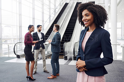 Buy stock photo Cropped shot of an attractive young businesswoman standing in a modern workplace with her colleagues in the background