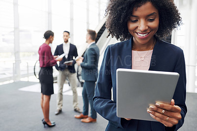 Buy stock photo Cropped shot of an attractive young businesswoman using a digital tablet in an office with her colleagues standing in the background