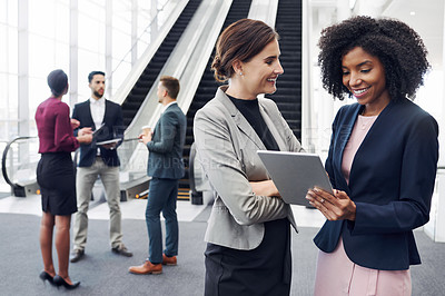 Buy stock photo Cropped shot of two attractive young businesswomen using a digital tablet in an office with their colleagues in the background