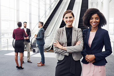 Buy stock photo Cropped portrait of two attractive young businesswomen standing in a office with their colleagues in the background