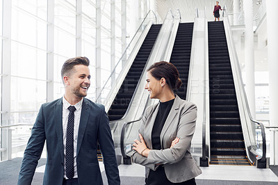 Buy stock photo Cropped shot of a handsome young businessman talking to his colleague while walking past her in a modern workplace