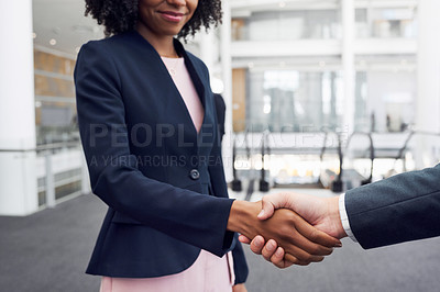 Buy stock photo Cropped shot of two unrecognizable young businesspeople shaking hands while standing in a modern workplace