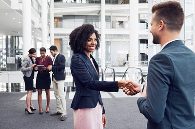 Buy stock photo Cropped shot of two young businesspeople shaking hands in an office workplace with their colleagues in the background