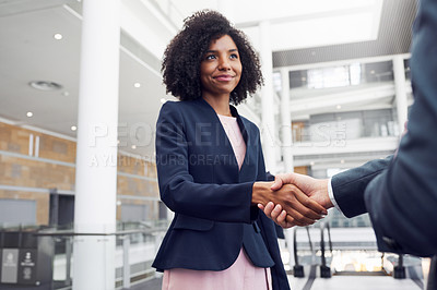 Buy stock photo Cropped shot of an attractive young businesswoman shaking hands with a businessman in a modern workplace
