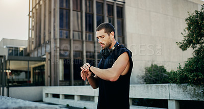 Buy stock photo Shot of a young man looking at his watch while exercising in the city