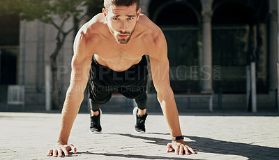 Buy stock photo Shot of a young man doing pushups during his workout in the city