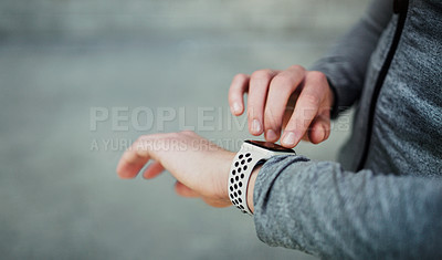 Buy stock photo Cropped shot of an unrecognizable man looking at his watch while exercising in the city